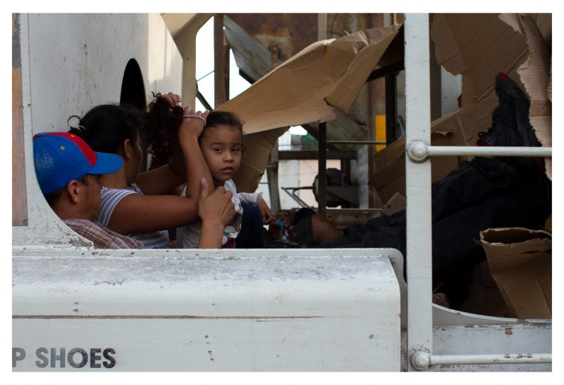 "Arriaga, Chiapas. 6 May 2014. While riding the train, a Honduran child turns her gaze at me as she gets her hair done. She is from San Pedro Sula, the most violent city in the world, where hope is non-existent and death, confused with dust, seizes the souls of ""guiros"", as kids are called in Honduras. Faced with the choice of either becoming paid assassins for local gangs, or killed because of refusing to do so, children flee their country. Sending an unaccompanied child from Honduras to the border of the United States can cost up to $5,000 USD. This cost includes travelling in luxury buses through Mexico, and the payments made to cartels and Mexican authorities in order to cross the country without risking detention."